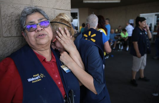 WalMart employees react after an active shooter opened fire at the store near Cielo Vista Mall in El Paso Saturday.