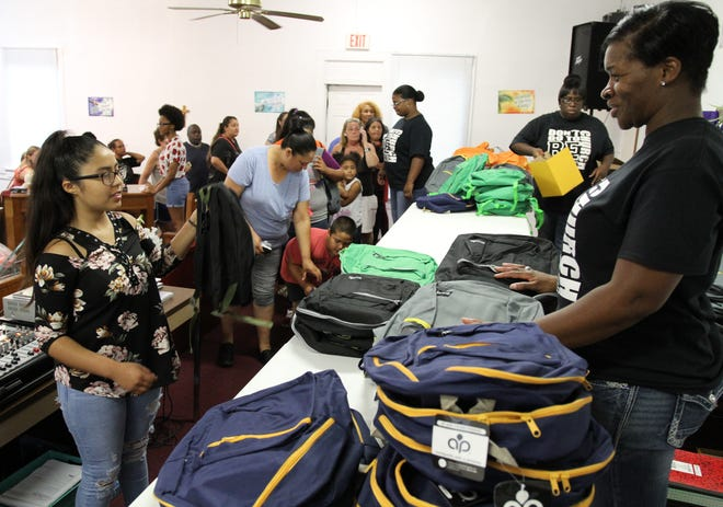 A girl picks a backpack Saturday, Aug. 3, 2019, that was filled with school supplies at the St. Matthew Baptist Church back to school event.