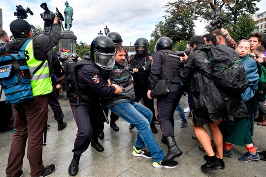 Riot police officers detain a participant of an unsanctioned rally urging fair elections at Moscow's Pushkinskaya Square on August 3, 2019. - The rally is the latest in a series of demonstrations after officials refused to let popular opposition candidates run in next month's city parliament elections.