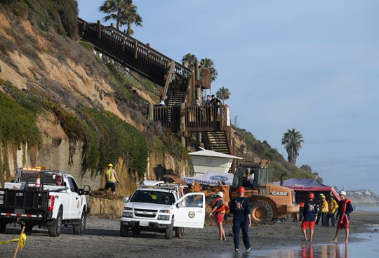 Lifeguards and search and rescue personnel work at the site of a cliff collapse at a popular beach Friday, Aug. 2, 2019, in Encinitas, Calif.