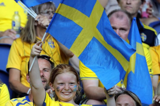 A young Swedish soccer fan holds his the nation's national flag ahead of the France 2019 Women's World Cup round of sixteen match between Sweden and Canada, on June 24, 2019.