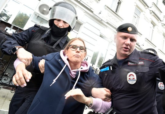 Police officers detain an opposition candidate and lawyer at the Foundation for Fighting Corruption Lyubov Sobol in the center of Moscow, Russia, Saturday, Aug. 3, 2019.