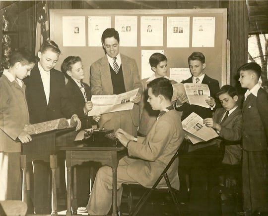 In one of his early years on the faculty of Gibbons Hall, adviser Joe Lalley and the Gibbons Hall Class of 1952 review the latest issue of The Cardinal.  To the left of Lalley are an unidentified student, Brad Moore, and Wriston Thompson.  At right are Tom King, Kerry Rudy, Larry Redmond (seated), and Leicester Chapman.  Dick Arnold sits at the typewriter, perhaps preparing the lead story for the next issue.
