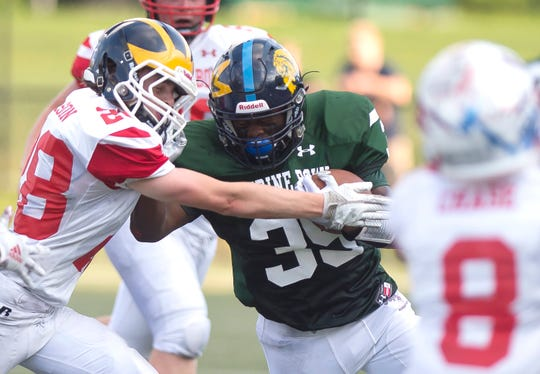 Mount Mansfield's Jehric Hackney, center, stiff-arms New Hampshire's Jack Wixson during the 2019 Shrine Maple Sugar Bowl at Castleton University on Saturday, Aug. 3.