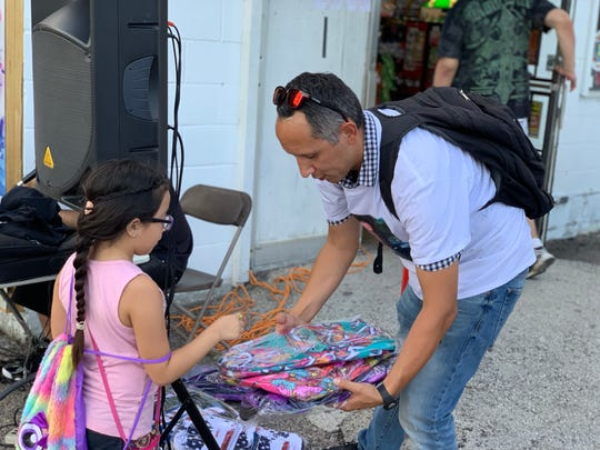 Eric Tunchez passes out backpacks to kids at tje Fiesta de Selena Mural event on Saturday, Aug. 3, 2019.