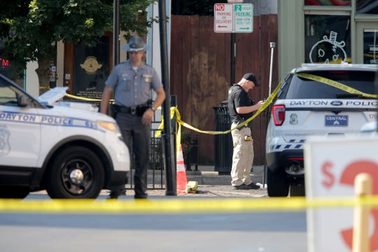 Authorities investigate the scene of a mass shooting that left ten dead, including the shooter, 26 injured along the 400 block of E. Fifth Street, Sunday, Aug. 4, 2019, in Dayton, Ohio.