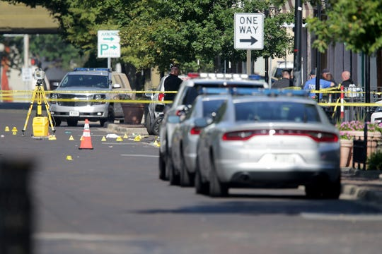 Authorities investigate the scene of a mass shooting that left at least nine dead and 26 injured along the 400 block of E. Fifth Street, Sunday, Aug. 4, 2019, in Dayton, Ohio.