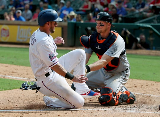 Detroit Tigers catcher John Hicks tags out Texas Rangers Jeff Mathis at home during the seventh inning Sunday, Aug 4, 2019, in Arlington, Texas.