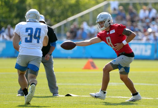 Detroit Lions quarterback David Fales hands off to Zach Zenner during training camp Sunday, August 4, 2019 in Allen Park.