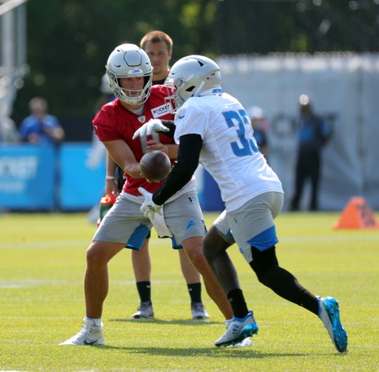 Detroit Lions quarterback Matthew Stafford hands off to Kerryon Johnson during training camp Sunday, August 4, 2019 in Allen Park.