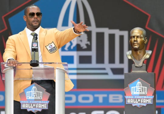 Former NFL player Ty Law speaks during the induction ceremony at the Pro Football Hall of Fame on Saturday.