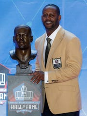 Former NFL player Ty Law poses with a bust of himself.
