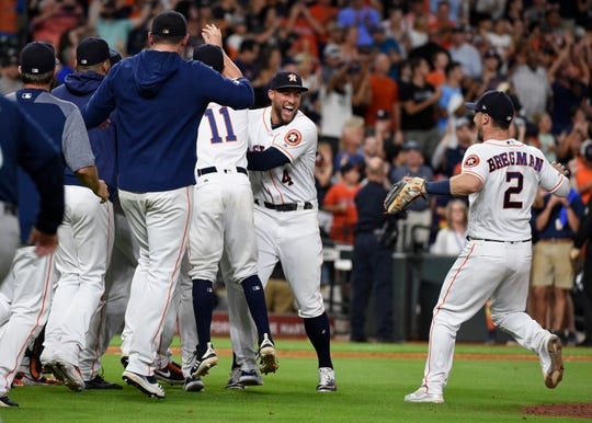 Houston's George Springer (4), Alex Bregman (2) and teammates celebrate the team's win and four-pitcher combined no-hitter Saturday.