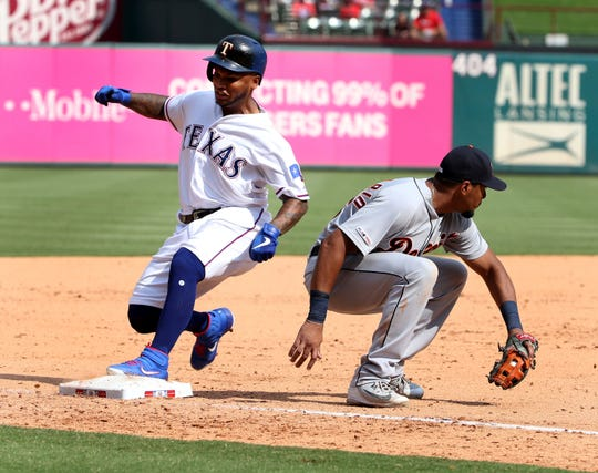 Texas Rangers' Willie Calhoun, left, gets to third in front of Detroit Tigers third baseman Jeimer Candelario for a three-run triple during the seventh inning on Sunday.