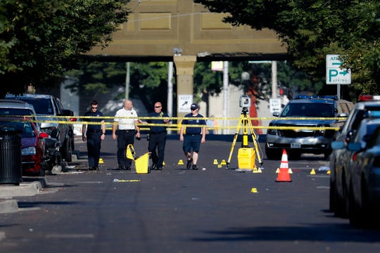 Authorities walk among evidence markers at the scene of a mass shooting, Sunday in Dayton, Ohio.
