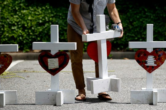 A volunteer prepares to place crosses for victims of a mass shooting at a municipal building in Virginia Beach, Va., June 2.