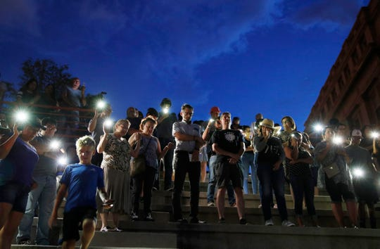 People attend a vigil for victims of the shooting Saturday, in El Paso, Texas.