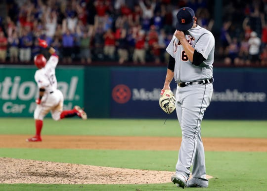 The Detroit Tigers' Nick Ramirez wipes his face after giving up a solo home run to the Texas Rangers' Rougned Odor in the 10th inning.