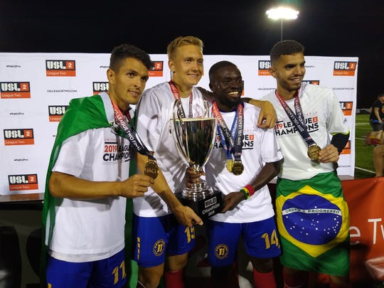 Flint City Bucks players Yuri Farkas Gugliemi, left; Charlie Booth, Foster Appiah and Gustavo Vasconcelos share a moment with the USL League 2 trophy after Saturday's 1-0 extra-time victory over Reading United AC before 7,198 fans at Atwood Stadium.