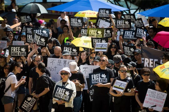 People hold signs during a rally in support of Hong Kong anti-extradition bill protesters, in Vancouver, British Columbia, Saturday, Aug. 3, 2019. The demonstration was one of many held in cities across Canada Saturday.