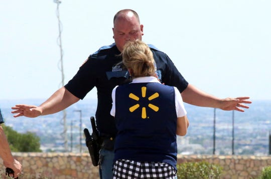An El Paso police officer talks to a store employee following a shooting  at a shopping mall in El Paso, Texas, on Saturday, Aug. 3, 2019.   Multiple people were killed and one person was in custody after a shooter went on a rampage at a shopping mall, police in the Texas border town of El Paso said.