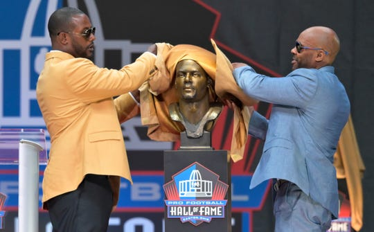 Former NFL player Ty Law, left, and his presenter, Byron Washington, unveil a bust of Law during the induction ceremony.