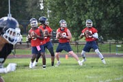 Quarterbacks Derrick Ponder, Jalon Jones and Quincy Casey look to pass the ball in individual drills at fall camp Saturday, Aug. 3