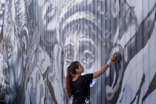 Paola Delfin of Mexico City, Mexico, works on her mural at 110 Walnut st, Friday, Aug. 2, 2019 in Lafayette.