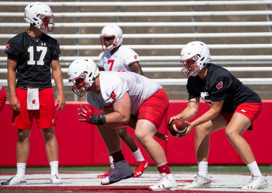 Center Tyler Biadasz works with freshman quarterback Graham Mertz at the start of training camp.