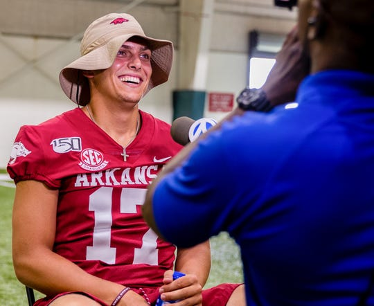 Razorback junior quarterback Nick Starkel (17) of Argyle, Texas, answers questions from reporters at the Arkansas Razorbacks' Media Day Saturday afternoon in Fayetteville.