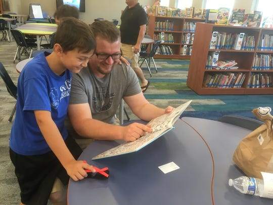 "Derek Decker, left, points out a ""Where's Waldo"" book to his rising fifth-grade son, Dameon, at the library at the new Rocky Fork Elementary during Sunday's open house. The first abbreviated day of the school year will be Tuesday and the first full day will be Thursday."