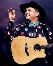 """Garth Brooks waves to fans in the Grand Ole Orpy House balcony who shouted, """"We love you Garth,"""" during the TNN Music News Awards show June 10, 1991. One of his biggest hits is """"The Dance."""""""