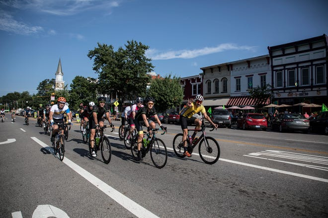 Pelotonia riders make their way through Granville during the 11th annual bike ride that raises money for cancer research.  Each year supporters fill the sidewalks of Granville to rally the riders on with cow bells, signs and cheers.
