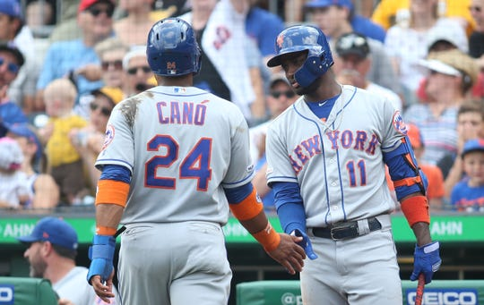 Aug 4, 2019; Pittsburgh, PA, USA;  New York Mets third  baseman Adeiny Hechavarria (11) greets second baseman Robinson Cano (24) after Cano scored a run against the Pittsburgh Pirates during the third inning at PNC Park.