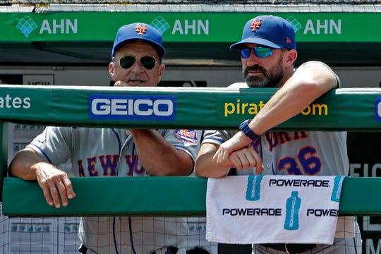 New York Mets manager Mickey Callaway, right, and bench coach Jim Riggleman stand in the dugout during a baseball game against the Pittsburgh Pirates in Pittsburgh, Sunday, Aug. 4, 2019.