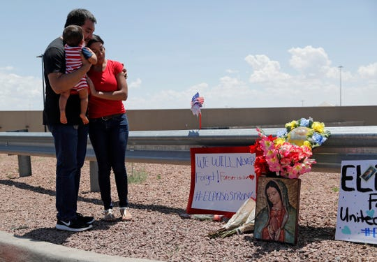 Dr. Julio Novoa, left, and Danielle Novoa, right, visit a makeshift memorial with their 10-month-old son Ricard Novoa at the scene of a mass shooting at a shopping complex Sunday, Aug. 4, 2019, in El Paso, Texas. (AP Photo/John Locher)