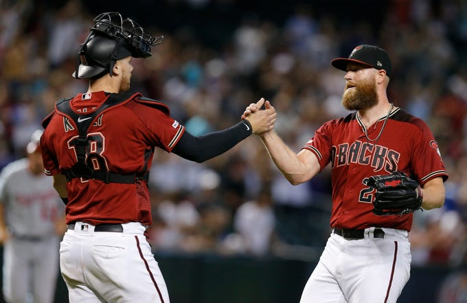 Arizona Diamondbacks' Archie Bradley and Carson Kelly (18) celebrate after defeating the Washington Nationals 7-5 during a baseball game, Sunday, Aug. 4, 2019, in Phoenix.
