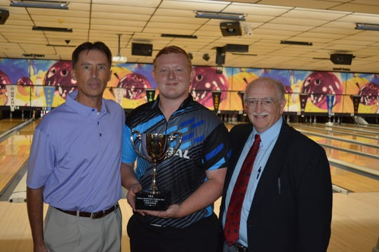 Darrin Armel, general manager of Colony Park Lanes North, left, and Russ Mils, Professional Bowlers Association East Region director, right, present the 2019 PBA Bowlers Supply/Storm Products Open trophy to 17-year-old Anthony Neuer of Lewisburg, Union County.