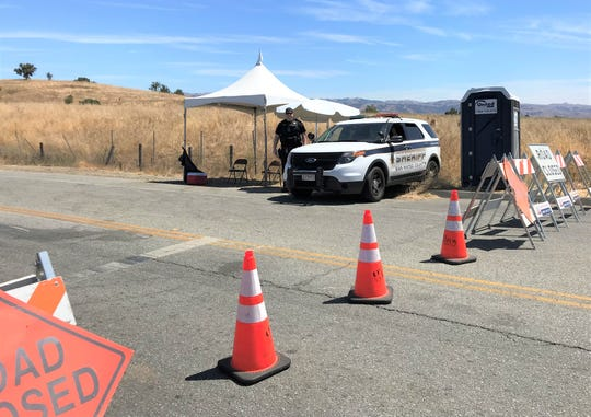 An officer monitors a closure at the corner of Santa Teresa Boulevard and Miller Avenue in Gilroy on Saturday. The area remains closed while law enforcement investigates the shooting Sunday, July 28 at the Gilroy Garlic Festival.
