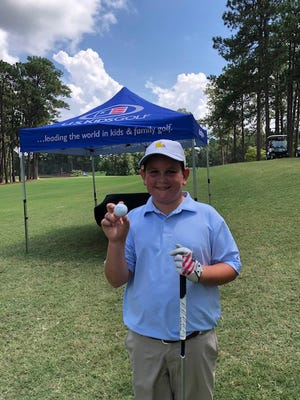 Bossier City's Hudson Greene shows off the ball that helped him make a hole-in-one during the U.S. Kids World Championships at Pinehurst on Saturday.