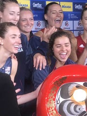 The USA Women's volleyball team celebrates with a  traditional Daruma doll to accompany them on their year-long journey to the Japanese capital for the Olympic Games.