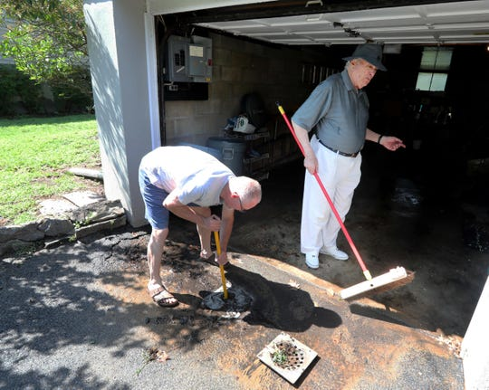 Reza Rezvani, left, helps his neighbor Hal Kleinman unclog a drain after a water main break caused minor flooding on Normal Rd. in New Rochelle Aug. 4, 2019. An eight in inch main burst causing several inches of water to flood several garages in homes on the street.