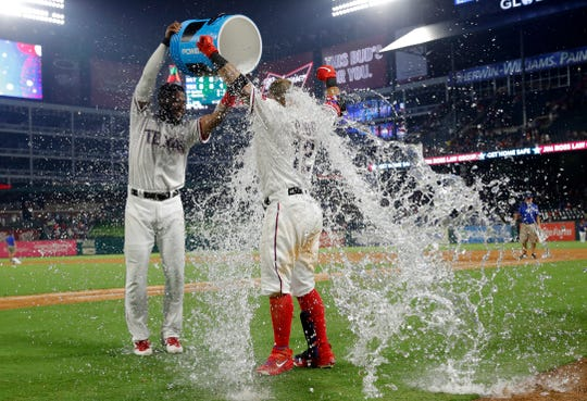 Texas Rangers' Elvis Andrus, left, douses Rougned Odor after the Rangers' 5-4 win against the Detroit Tigers a baseball game in Arlington, Texas, Saturday, Aug. 3, 2019. Odor hit a solo home run off of Tigers relief pitcher Nick Ramirez in the 10th inning. (AP Photo/Tony Gutierrez)