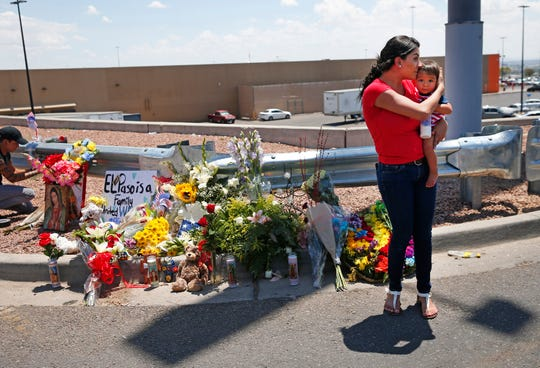 Daniella Novoa holds her son Richard, 10-months, after placing flowers and a poster outside Walmart in El Paso on Aug. 4, 2019.