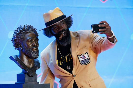 Former NFL player Ed Reed takes a selfie with his Pro Football Hall of Fame bust during inductions at the hall Saturday, Aug. 3, 2019, in Canton, Ohio.