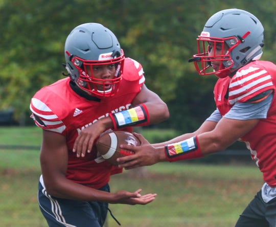 Palmetto High School running back Raheim Thompson, left, takes a handoff from quarterback Landon Owens during practice in August.
