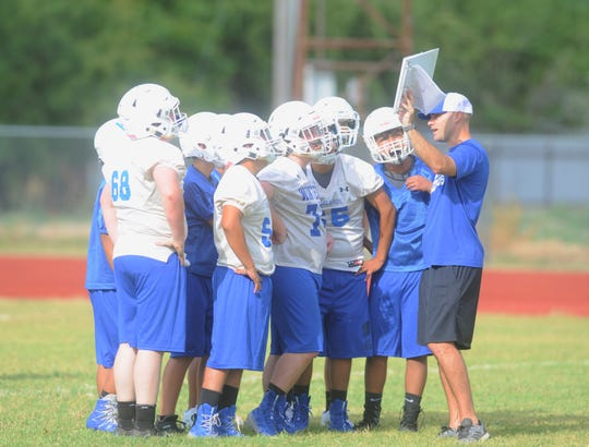 Winters football coach Matt McCarty shows the offense a play during the first day of practice Monday at the Blizzards' practice field.