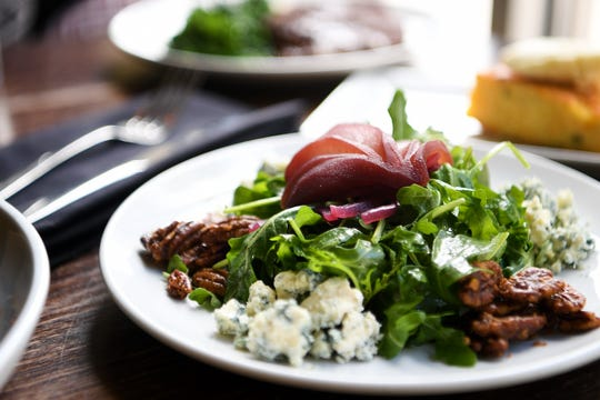 The arugula salad at The Blackbird in downtown Asheville is baby arugula, red wine poached pair, pickled red onion, spiced pecans, blue cheese, pear vinaigrette and a red wine reduction.