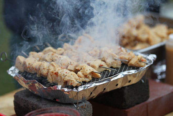 Chicken spiedies cook on a grill during the 2019 Spiedie Fest.