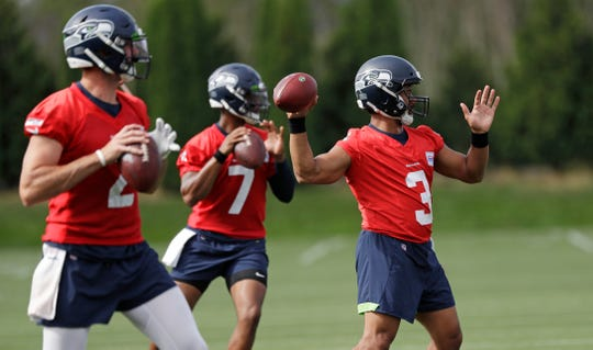 Seattle Seahawks starting quarterback Russell Wilson (3) leads Paxton Lynch (2) and Geno Smith (7) in a quarterbacks drill at an NFL football training camp Thursday, Aug. 1, 2019, in Renton, Wash.
